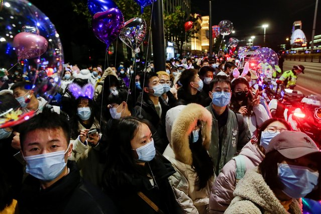 People gather to celebrate the arrival of the new year during the coronavirus disease (COVID-19) outbreak in Wuhan, China on December 31, 2020. (Photo by Tingshu Wang/Reuters)