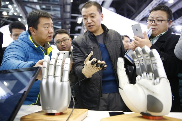 A visitor experiences to control a dexterous robotic hand during the World Robot Conference at China national convention center in Beijing city, China, 23 November 2015. The conference is held during 23-25 November 2015 including the forum, exhibition and world adolescent robot contest. (Photo by Wu Hong/EPA)