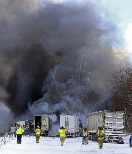 Emergency personnel watch as fireworks ignite at the scene of a fiery crash that closed both sides of Interstate 94, Friday, January 9, 2015, between mile markers 88 and 92 in eastern Kalamazoo County, near Galesburg, Mich. State police say at least one person has died in the series of crashes involving roughly 150 vehicles, including at least two semi-trucks carrying fireworks and other hazardous materials. (Photo by Mark Bugnaski/AP Photo/Kalamazoo Gazette-MLive Media Group)