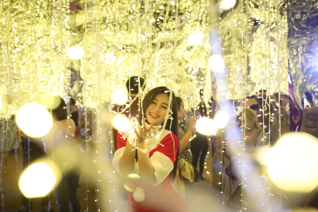 A woman dressed as Santa Claus poses for a picture during the Christmas season in front of a shopping center in Bangkok, Thailand on December 24, 2020. (Photo by Soe Zeya Tun/Reuters)