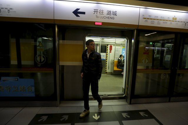 An Zi walks out from a subway car, on his way to work, in Beijing, November 12, 2015. An, a movie producer, moved to Dongsanqi village in Changping this year. His commute to work can take about 2 hours, with transportation costs topping 200 yuan a month, or about a fifth of his monthly rent. (Photo by Jason Lee/Reuters)