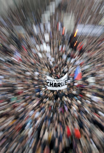 """Citizens carrying a banner which reads, """"We are Charlie"""" take part in a Hundreds of thousands of French citizens solidarity march (Marche Republicaine) in the streets of Paris January 11, 2015. (Photo by Eric Gaillard/Reuters)"""