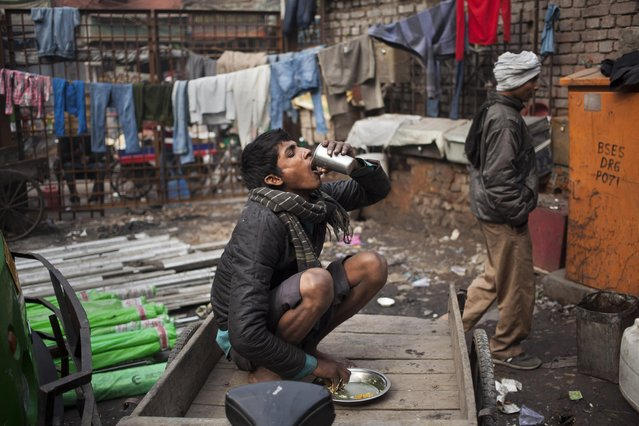 "An Indian migrant laborer drinks water after finishing his lunch at old quarters of Delhi, India, Monday, January 12, 2015. Migrant laborers, also known in the city as ""pavement dwellers"", sleep in the street of the Indian capital every night. (Photo by Tsering Topgyal/AP Photo)"