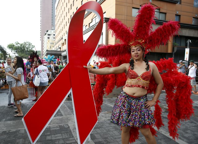 A Filipino transgender woman holds a huge red ribbon symbolizing fight against the HIV virus as she poses before photographers, during a World Aids Day celebration in Manila, Philippines, December 1, 2015. (Photo by Erik De Castro/Reuters)