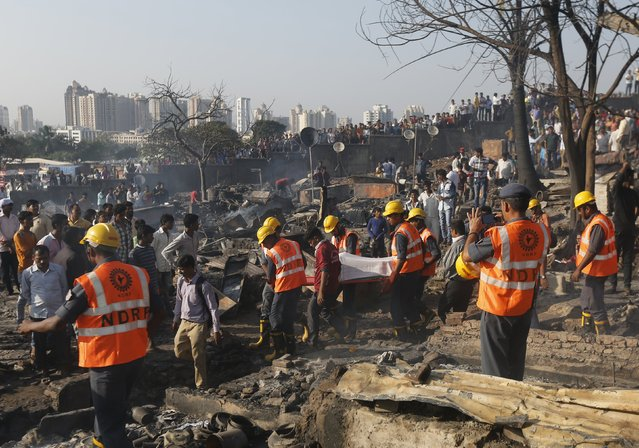 Rescue workers carry the body of a victim after a fire occurred in a slum area in Mumbai, India, December 7, 2015. (Photo by Shailesh Andrade/Reuters)
