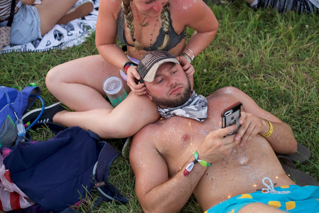 Brandon Hall, 33, uses his iPhone during the Firefly Music Festival in Dover, Delaware June 14, 2018. (Photo by Mark Makela/Reuters)