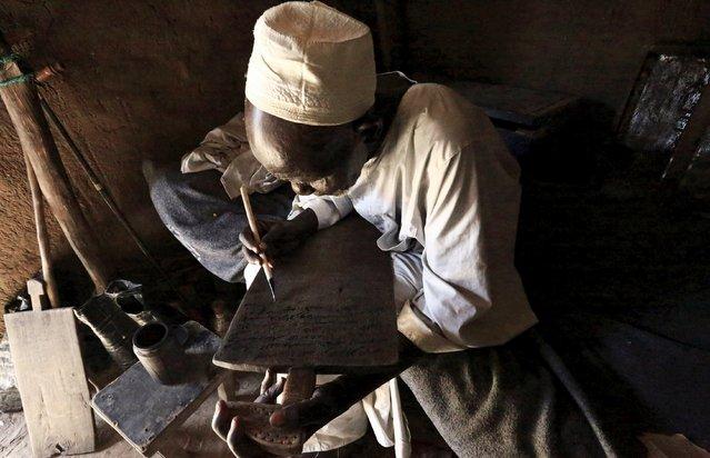 An internally displaced man writes the Koran using Arabic alphabet inside his shelter in Kalma camp in Nyala, South Darfur, Sudan, November 22, 2015. (Photo by Mohamed Nureldin Abdallah/Reuters)
