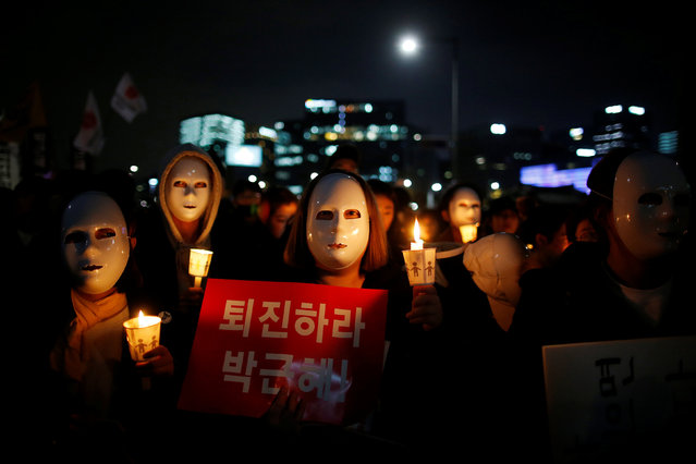 """People march toward the Presidential Blue House during a rally calling for President Park Geun-hye to step down in central Seoul, South Korea, November 12, 2016. The sign reads: """"Step down Park Geun-hye"""". (Photo by Kim Hong-Ji/Reuters)"""