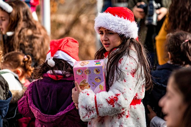 Children attend a Christmas celebration event by Syriac Christians in the town of al-Qahtaniyah in Syria's northeastern Hasakeh province near the Turkish border, on December 29, 2020. (Photo by Delil Souleiman/AFP Photo)