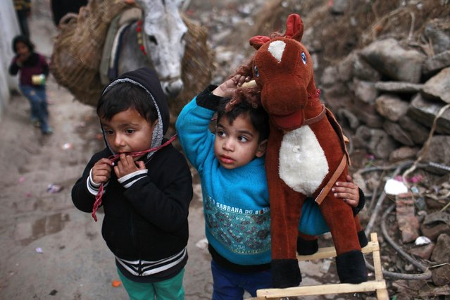A young boy carries his rocking horse toy on his shoulder next to another boy in an ally inside a Christian colony in Islamabad January 20, 2015. (Photo by Sara Farid/Reuters)