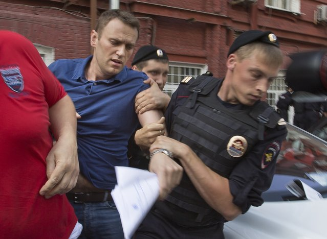 Police officers detain Russian opposition leader Alexei Navalny, left, in Moscow, Russia, Wednesday, July 10, 2013. Navalny was briefly detained by police after he spoke to a crowd of supporters outside the headquarters of Moscow's election commission. Navalny on Wednesday submitted documents to register as a candidate in the mayoral election. (Photo by Alexander Zemlianichenko/AP Photo)