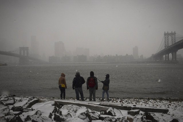 People stand at the shore of the East River and New York Harbor in Brooklyn in New York City as the skyline of lower Manhattan is obscured in falling snow between the Brooklyn Bridge (L) and Manhattan Bridge (R) in later afternoon January 26, 2015. (Photo by Stephanie Keith/Reuters)
