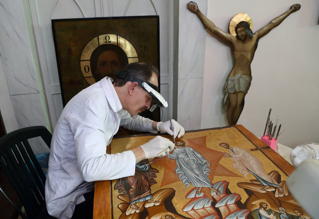 Venizelos Gavrilakis, a senior restorer and conservator from Thessaloniki, Greece, works to clean and restore a 16th century Byzantine Christian icon at a Greek Orthodox church where he set up his laboratory in Istanbul, Turkey on January 26, 2021. (Photo by Murad Sezer/Reuters)