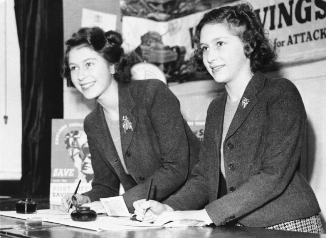 Princesses Elizabeth, left, and Margaret Rose sign their one-pound savings certificates after buying the first two as they were made available to the public, January 27, 1943. (Photo by AP Photo)