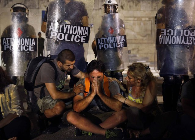 Municipal public school guard Yiorgos Avramidis, 43, married with two children of three and six, from the northern Greek town of Edessa, is comforted by colleagues in front of a police line guarding the Greek parliament in Athens, as Greece's shaky coalition government scraped through a vote on a bill to sack public sector workers, on July 17, 2013. The bill includes deeply divisive plans for a transfer and layoff scheme for 25,000 public workers - mainly teachers and municipal police - that had triggered a week of almost daily marches, rallies and strikes in protest. Avramidis is one of the more than 2,000 public school guards who lost their jobs. (Photo by Yannis Behrakis/Reuters)