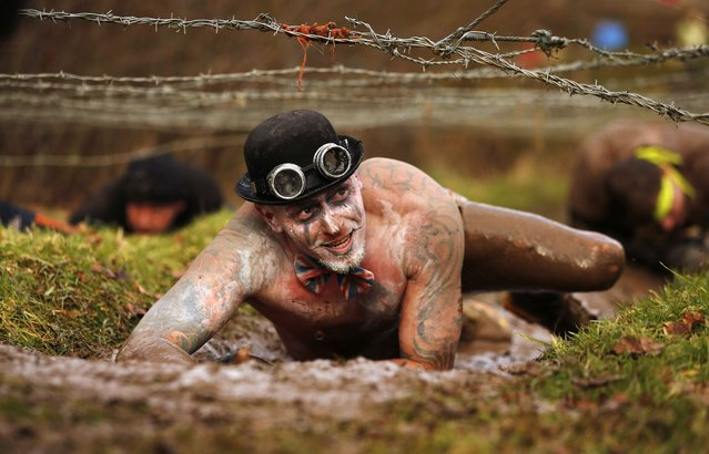 A competitor crawls beneath barbed wire during the Tough Guy event in Perton, central England February 1, 2015. (Photo by Phil Noble/Reuters)