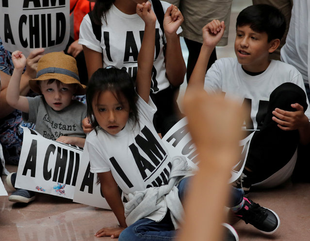 """Children and family members take part in a sit-in following a march to mark """"the court-ordered deadline for the Trump Administration to reunify thousands of families separated at the border, in Washington, U.S., July 26, 2018. (Photo by Carlos Barria/Reuters)"""