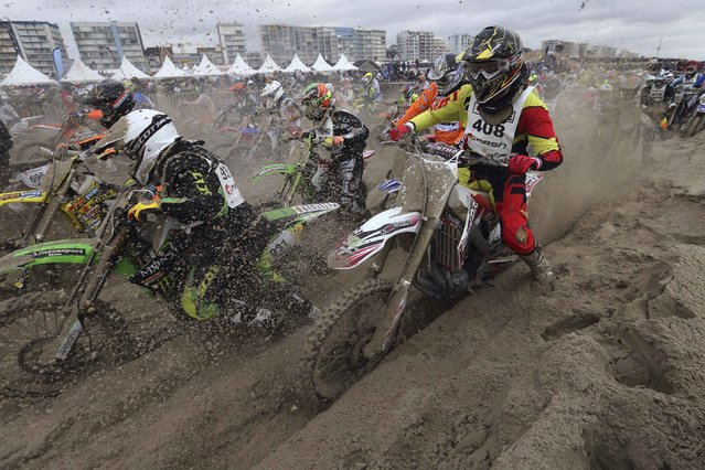 """Bikers push their motorbikes during a traffic block as they take part in the """"Enduropale"""" motorcycle endurance race on the beach of Le Touquet, northern France, February 1, 2015. (Photo by Pascal Rossignol/Reuters)"""