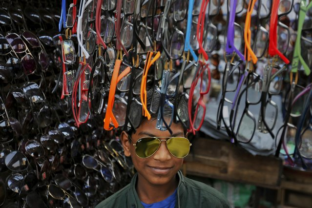 A Bangladeshi roadside vendor wears sunglasses to attract customers to his shop in Dhaka, Bangladesh, Monday, December 28, 2015. (Photo by A.M. Ahad/AP Photo)