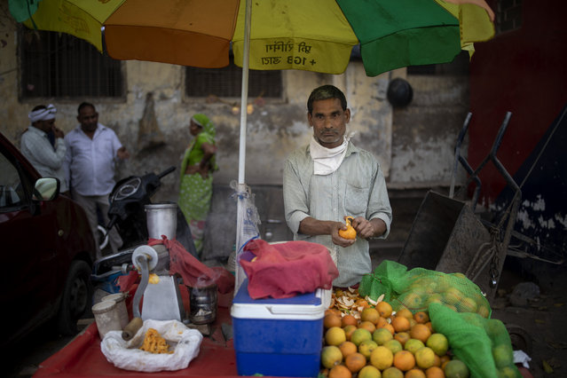 Ganesh Chaurasia, 42, a roadside juice vendor peels an orange as he waits for customers in New Delhi, India, Tuesday, March 16, 2021. Chaurasia says the lockdown plummeted his income and pushed his family, which is still struggling to make their ends meet, into economic despair. Street vendors like Chaurasia represent 4% of the urban workforce across India. (Photo by Altaf Qadri/AP Photo)