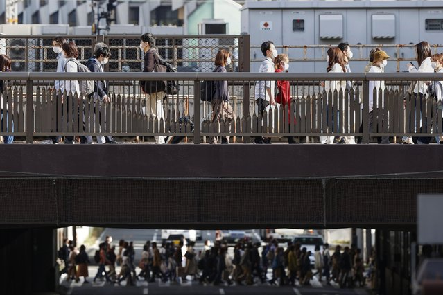 People wear face masks as they make their way in Osaka, western Japan Wednesday, March 31, 2021. Japan is set to designate Osaka and two other prefectures for new virus control steps Thursday as infections in those areas rise less than four months before the Tokyo Olympics. (Photo by Kyodo News via AP Photo)