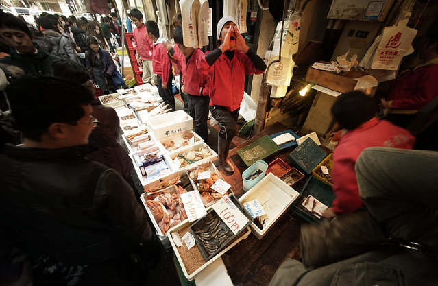 """In this December 31, 2015 file photo, fish store vendors sell fresh seafood to shoppers who  look for ingredients for """"osechi"""" or Japanese traditional New Year dishes, near Tsukiji fish market in Tokyo. In one of the biggest of Japan's many New Year holiday rituals, early on Tuesday, January 5, 2016, Tokyo's Tsukiji market will auction off with much fanfare a huge, glistening tuna, likely destined for one of the big sushi chains. If all goes as planned, it will be the last such auction at 80-year-old Tsukiji. (Photo by Eugene Hoshiko/AP Photo)"""