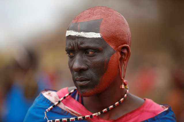 A Maasai master of ceremony painted with red ochre pigment takes part in an initiation into an age group ceremony near the town of Bisil, Kajiado county, Kenya on August 23, 2018. (Photo by Baz Ratner/Reuters)