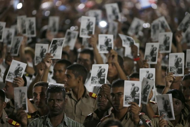 Cadets hold images of Cuba's late President Fidel Castro as they pay tribute to Castro at dusk at Revolution Square in Havana, Cuba, November 29, 2016. (Photo by Carlos Garcia Rawlins/Reuters)