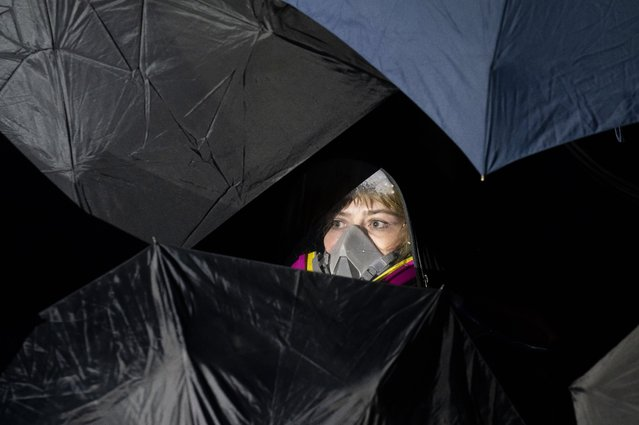 A demonstrator is behind umbrellas during a protest over Sunday's fatal shooting of Daunte Wright during a traffic stop, outside the Brooklyn Center Police Department on Wednesday, April 14, 2021, in Brooklyn Center, Minn. (Photo by John Minchillo/AP Photo)