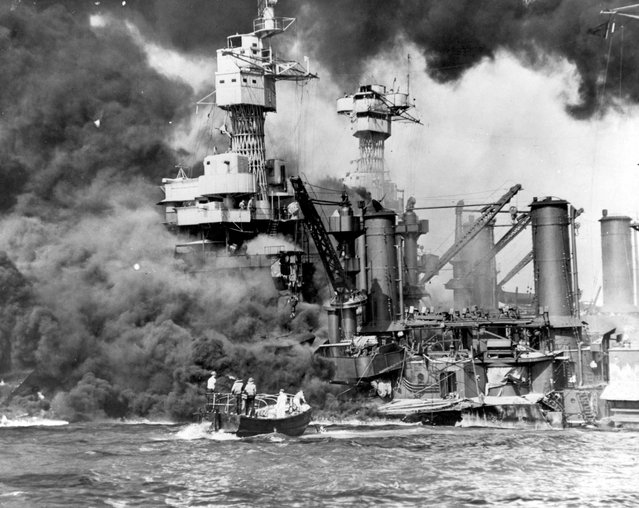 Sailors in a motor launch rescue a survivor from the water alongside the sunken battleship USS West Virginia during or shortly after the Japanese air raid on Pearl Harbor, Hawaii, U.S. December 7, 1941. (Photo by Reuters/U.S. Navy/National Archives)