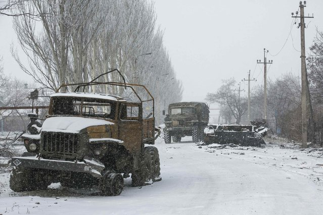 A truck used by separatist self-proclaimed Donetsk People's Republic drives by destroyed Ukrainian army vehicles in the town of Vuhlehirsk, about 10 km (6 miles) to the west of Debaltseve, February 16, 2015. (Photo by Baz Ratner/Reuters)