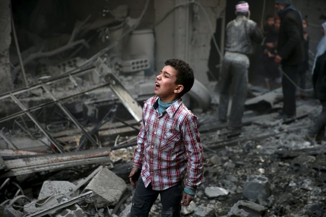 A boy reacts in a site hit by what activists said were airstrikes carried out by the Russian air force in the town of Douma, eastern Ghouta in Damascus, Syria January 10, 2016. (Photo by Bassam Khabieh/Reuters)