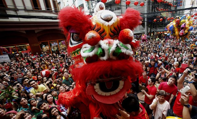 Revellers gather near lion dance performers as they celebrate Lunar New Year at Manila's Chinatown February 19, 2015. (Photo by Erik De Castro/Reuters)
