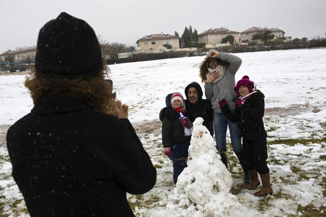 A family poses for a photograph next to a snowman in the southern Israeli city of Arad February 20, 2015. (Photo by Amir Cohen/Reuters)