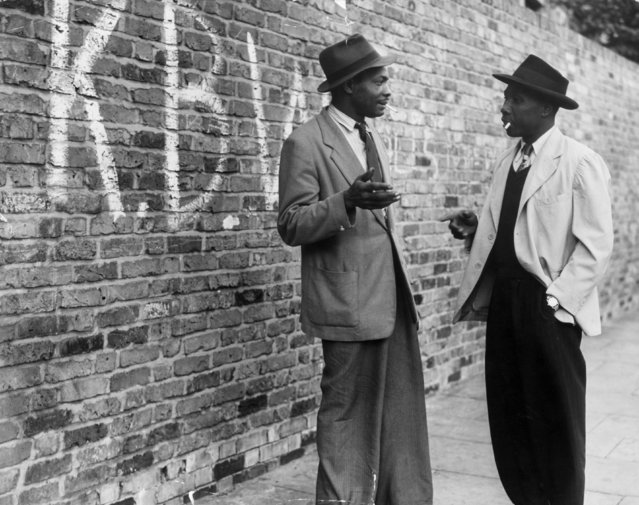 """Two Jamaican men talking in a street in Brixton, south London, 9th June 1952. The graffiti on the wall stands for """"Keep Britain White"""". (Photo by Express Newspapers/Getty Images)"""