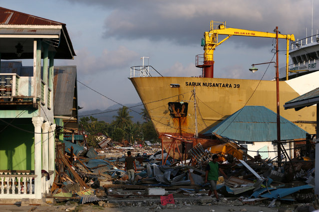 A local residents affected by the earthquake and tsunami walks next to a ship stranded on the shore in Wani, Donggala, Central Sulawesi, Indonesia, October 3, 2018. (Photo by Athit Perawongmetha/Reuters)