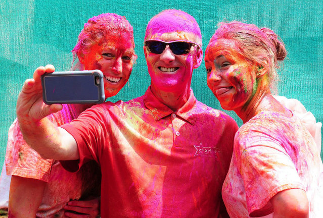 epa04649956 Tourists smeared with colors take selfies during the Holi Festival in Bangalore, India, 06 March 2015. Holi is celebrated at the end of the winter season on the last full moon day of the lunar month Phalguna (February or March) and its main day is celebrated by people throwing colored powder and colored water at each other.  EPA/JAGADEESH NV