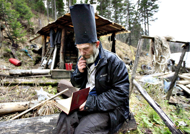 Former bargeman Viktor, 57, who refused to give his family name, reads the Bible while wearing a hat he made for this purpose, outside his wooden hut located in a forest some 55 km (34 miles) south of Russia's Siberian city of Krasnoyarsk, October 17, 2013. A decade ago, Viktor decided to lead the life of a hermit, and settled in this secluded forest area hidden from civilisation. He reads the Bible, and survives mainly on fish, berries, mushrooms and other food he can find. (Photo by Ilya Naymushin/Reuters)
