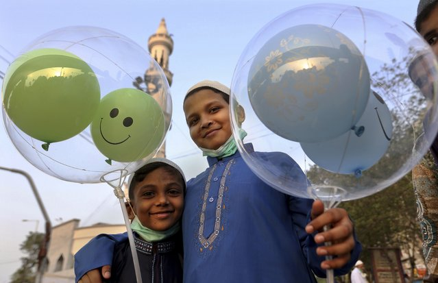 Muslim boys hold balloons after performing an Eid al-Fitr prayer at a mosque in Karachi, Pakistan, Thursday, May 13, 2021. Millions of Muslims across the world are marking a muted and gloomy holiday of Eid al-Fitr, the end of the fasting month of Ramadan - a usually joyous three-day celebration that has been significantly toned down as coronavirus cases soar. (Photo by Fareed Khan/AP Photo)