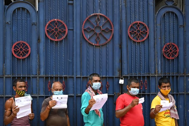 Workers hold documents as they wait for their turn to receive the first dose of Covishield vaccine against the Covid-19 coronavirus in a passenger bus converted into a mobile vaccination centre at a wholesale market in Kolkata on June 3, 2021. (Photo by Dibyangshu Sarkar/AFP Photo)
