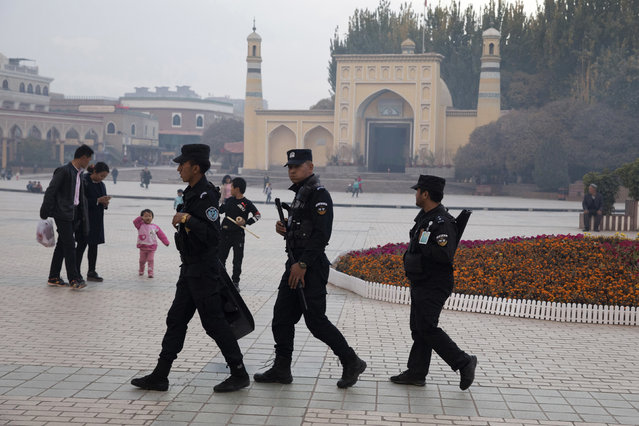 """In this November 4, 2017 file photo, Uighur security personnel patrol near the Id Kah Mosque in Kashgar in western China's Xinjiang region. China's northwestern region of Xinjiang has revised legislation to allow the detention of suspected extremists in """"education and training centers"""". The revisions come amid rising international concern over a harsh crackdown in Xinjiang that has led to as many as 1 million of China's Uighurs and other Muslim minorities being held in internment camps. (Photo by Ng Han Guan/AP Photo)"""