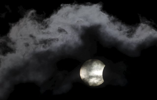 A partial solar eclipse is seen through clouds in Sarajevo March 20, 2015. (Photo by Dado Ruvic/Reuters)