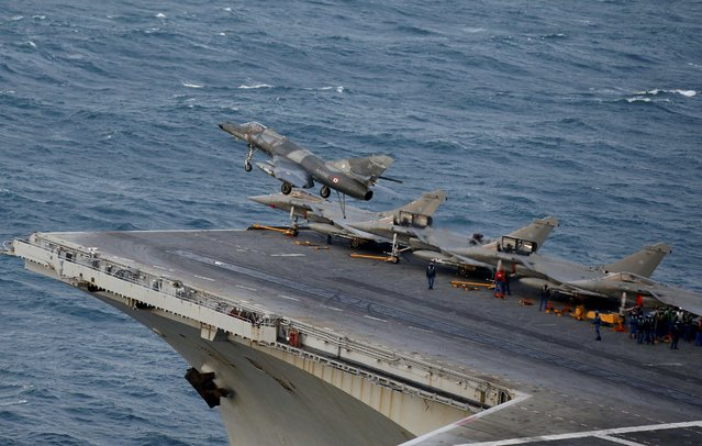 A Super Etendard fighter jet, with its hook extended after it missed its cable arrest landing, flies above the deck of France's Charles de Gaulle aircraft carrier as it returns from a mission in the Gulf, January 28, 2016. (Photo by Philippe Wojazer/Reuters)