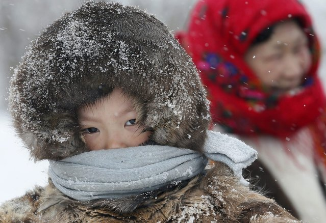In this photo taken on Sunday, March 15, 2015, a Nenets boy attends the Reindeer Herder's Day holiday in the city of Nadym, in Yamal-Nenets Region, 2500 kilometers (about 1553 miles) northeast of Moscow, Russia. (Photo by Dmitry Lovetsky/AP Photo)