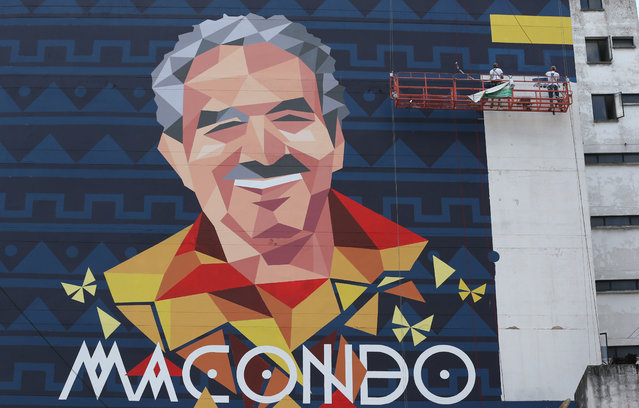 In this March 12, 2015 photo, street artists paint a mural of late writer Gabriel Garcia Marquez on the side of a building, in Bogota, Colombia. The city also recently commissioned, at a cost of around $10,000, an eight-story-high depiction of the late Colombian novelist and Nobel laureate. (Photo by Fernando Vergara/AP Photo)