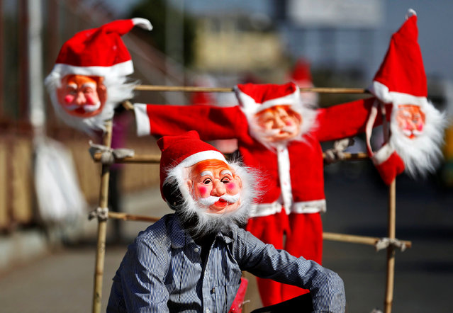 A vendor wears a Santa Claus mask to attract customers on a roadside in Ahmedabad, India, December 16, 2016. (Photo by Amit Dave/Reuters)