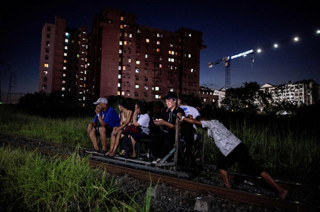 """This photo taken on October 19, 2018 shows a """"trolley boy"""" (R) pushing a home- made cart with passengers on a train track in Manila, Philippines. (Photo by Noel Celis/AFP Photo)"""