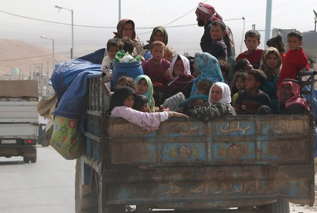 Civilians fleeing the recent fightings in their area sit at the back of a pickup truck with their belongings in the southern countryside of Aleppo, Syria October 21, 2015. (Photo by Hosam Katan/Reuters)
