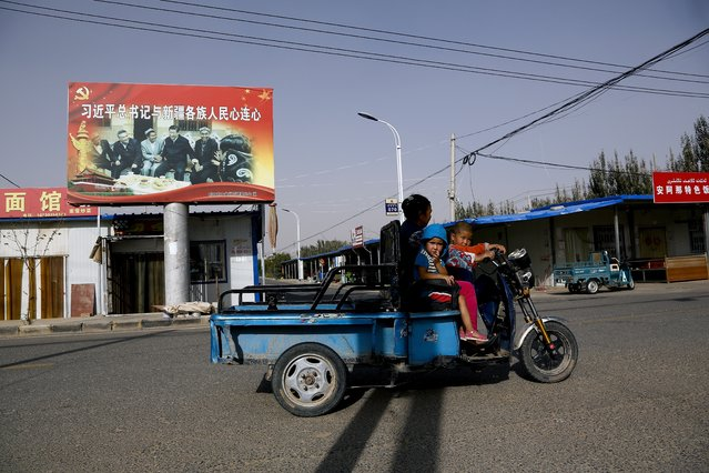 In this September 20, 2018, file photo, an Uighur woman shuttles school children on an electric scooter as they ride past a propaganda poster showing China's President Xi Jinping joining hands with a group of Uighur elders in Hotan, in western China's Xinjiang region. Under Chinese President Xi Jinping, the Uighur homeland has been blanketed with stifling surveillance, from armed checkpoints on street corners to facial-recognition-equipped CCTV cameras steadily surveying passers-by. Now, Uighurs say, they must live under the watchful eye of the ruling Communist Party even inside their own homes. (Photo by Ng Han Guan/AP Photo)