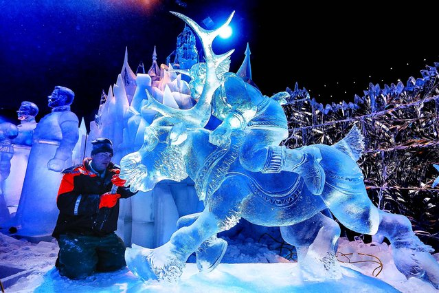 """Sculptor Sergey Aseev of Russia carves a sculpture based on Disney's newest movie """"Frozen"""" at the Snow and Ice Sculpture Festival in Bruges, Belgium, on November 20, 2013. Some 28 artists from all over the world made 55 sculptures out of 250 tons of ice depicting many characters from previous Disney movies. (Photo by Francois Lenoir/Reuters)"""